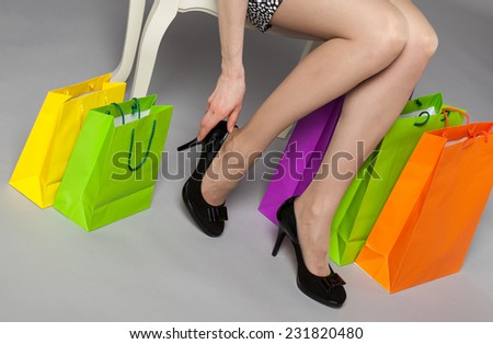 Unrecognizable young woman trying on new black shoes - studio shot - stock photo