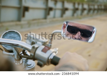 Unrecogonizable person Reflection image on mirror Biker man sits on bike and wearing black sunglasses On metal bridge background in perspective Empty copy space for inscription Hand on steering wheel - stock photo