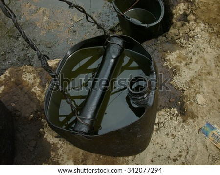 Unrefined crude oil is collected in oil drums at a heavily polluted, illegal oil field in Kadewan, East Java, Indonesia. - stock photo