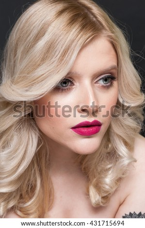 Unretouched raw studio beauty portrait of a blonde caucasian girl with curly hair, bright make up on dark background