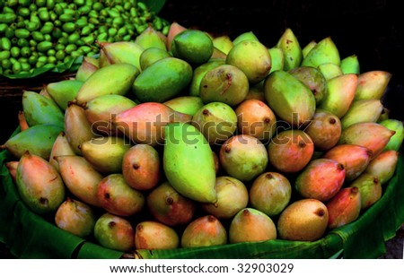Unripe Mangoes Stacked on a vendor cart