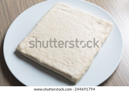 Unrolling dough on plate on table - stock photo