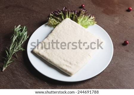 Unrolling dough with salad on plate - stock photo