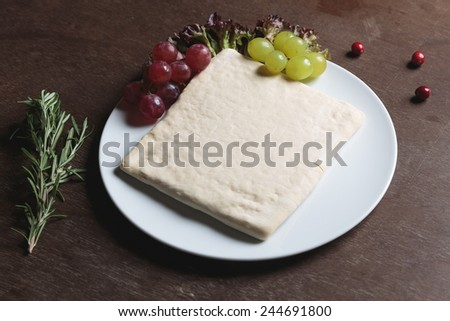 Unrolling dough with salad rosemarie and grape on plate - stock photo