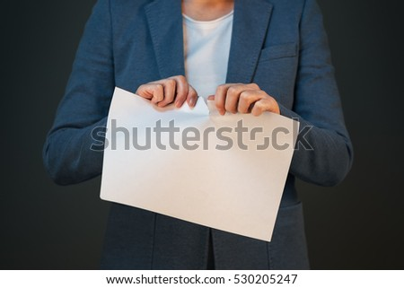 Unsatisfied and angry businesswoman tearing business legal agreement contract paper