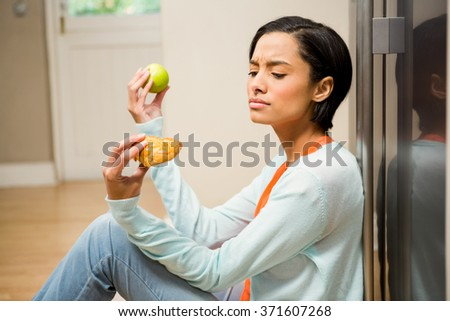 Unsettled brunette holding apple and dessert sitting on the floor in the kitchen - stock photo