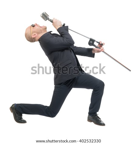Unshaven bald man in a gray suit and sunglasses holding a microphone and singing. Isolated - stock photo