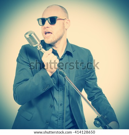 Unshaven bald man in a gray suit and sunglasses holding a microphone and singing. Toned