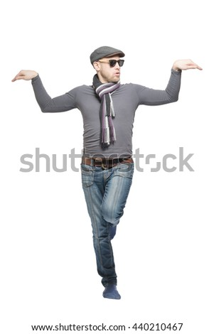 Unshaven bald man wearing a cap, jeans, sunglasses and a scarf dancing a strange dance. Isolated