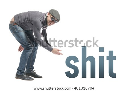 Unshaven bald man wearing a cap, jeans, sunglasses and scarf crouched and points to the inscription SHIT. Isolated - stock photo