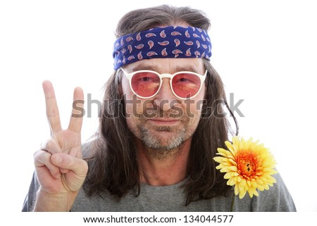 Unshaven male hippie with long shoulder length hair wearing a headband, yellow flower and rose coloured glasses making a peace sign with his fingers, head and shoulders portrait isolated on white