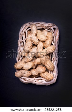 unshelled peanuts peanuts isolated in basket on black background - stock photo