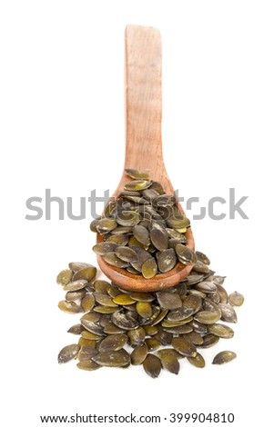 Unshelled pumpkin seeds in wooden spoon over white background - stock photo