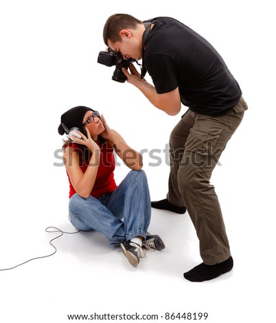 Unshod photographer taking picture from above of sitting female model with headphones and glasses