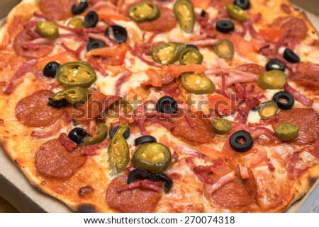 unsliced pepperoni pizza with olives close up view - stock photo