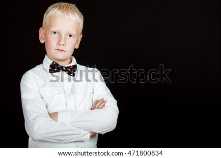 Unsmiling boy with arms crossed and dotted bow tie against a black background