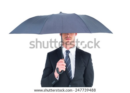 Unsmiling businessman sheltering under umbrella on white background