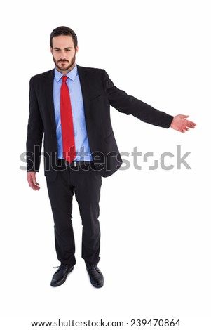 Unsmiling businessman showing something with his hand on white background - stock photo