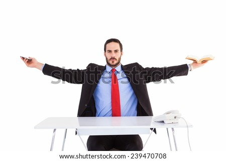 Unsmiling businessman sitting with arms outstretched on white background - stock photo