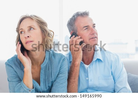 Unsmiling couple on their mobile phones on the couch at home in the living room