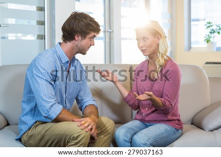 Unsmiling couple talking to each other in the therapist office