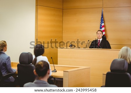 Unsmiling judge with american flag behind him in the court room - stock photo