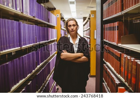 Unsmiling lawyer standing between shelfs with arms crossed in library - stock photo