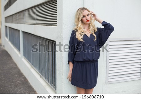 Unsmiling sexy blonde wearing classy dress posing outdoors against building - stock photo