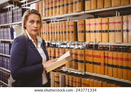 Unsmiling woman reading a book in library - stock photo