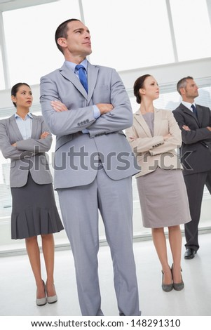 Unsmiling work team in bright office posing while looking in the same direction - stock photo