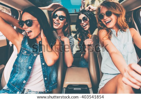 Unstoppable beauties. Four beautiful young cheerful women looking happy and playful while sitting in car - stock photo
