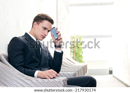 Unsuccessful job. Confident businessman sad while waiting for the client holding a cell phone next to a lowered head - stock photo