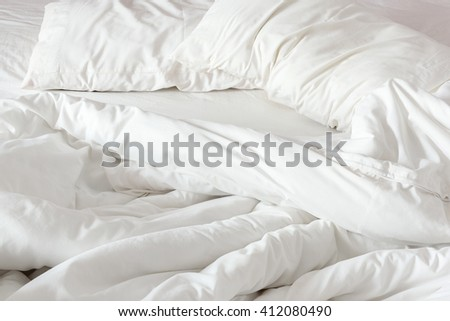 Untidy bedclothes : An unmade bed in a hotel bedroom with two white pillows and a blanket. Bedclothes are not neatly arranged for new guests / customers / visitors to  sleep in. - stock photo