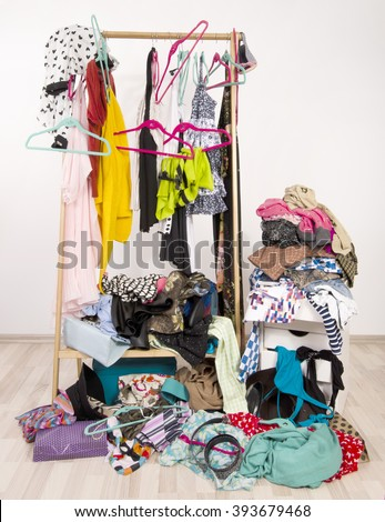 Untidy cluttered woman wardrobe with colorful clothes and accessories. Messy rack of clothes and hangers with a big pile thrown on the ground. - stock photo