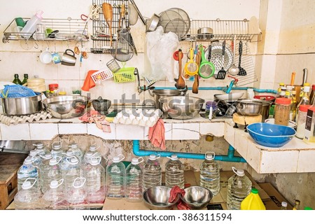 Untidy Kitchenware ; Pile of dirty dishes in sink and gallon water under the counter in the kitchen - stock photo