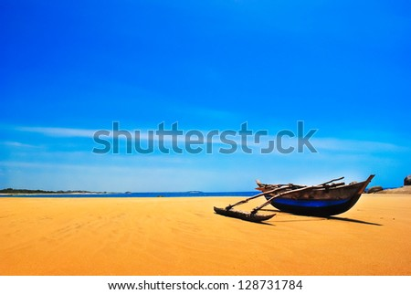 Untouched tropical beach with palms and fishing boats in - stock photo