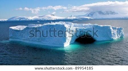 Unusual Antarctic iceberg in blue colours with coast and ocean during summer - stock photo