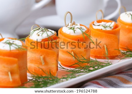 Unusual appetizer of fresh carrot rolls with cream cheese and dill on the table. horizontal  - stock photo