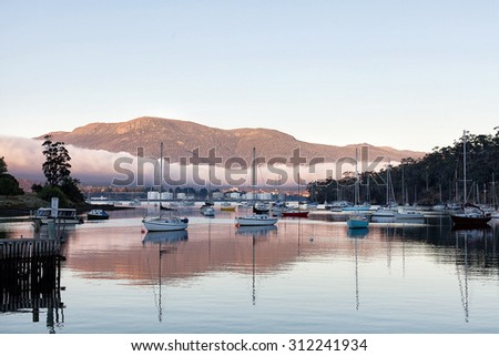 Unusual fog bank drifts down the Derwent River, Hobart, Tasmania, with Mount Wellington in background and Geilston Bay yacht harbour in foreground - stock photo