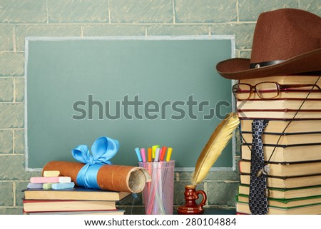 Unusual jesting teacher, books, quill, pen, scroll, chalk before blackboard with copy space - stock photo