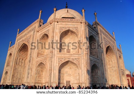 Unusual perspective of Taj Mahal at Agra, India drenched by the setting sun. It's amazing to see the scale of this magnificent structure compared to people. Also visible are some intricate artwork.