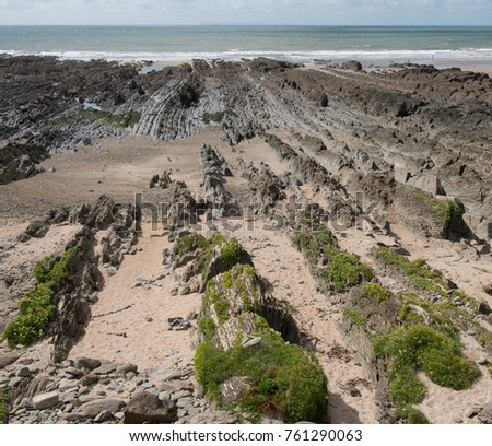 Unusual Rock Formations on Croyde Beach at Low Tide with the Atlantic Ocean in the Background on the South West Coast Path in Rural Devon, England, UK