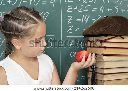 Unusual school concept, schoolgirl with apple and books as a parody on a teacher - stock photo