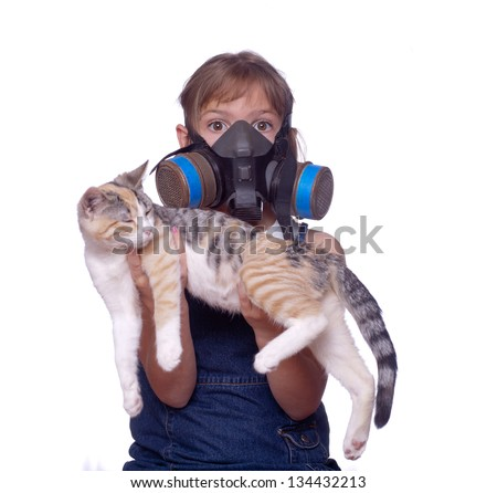 Unusual shot of a kid dealing with pet allergies by wearing a gasmask while holding her cat