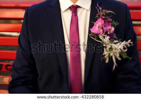 unusual violet boutonnieres with orchids and tie on luxury suit on groom close-up - stock photo
