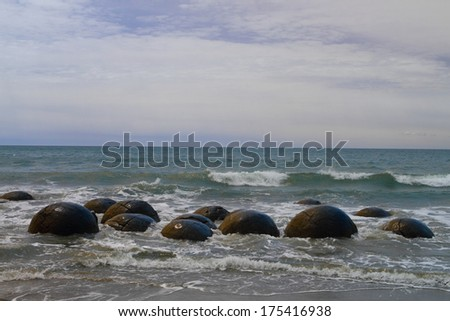 Unusually large and spherical Moeraki boulders lying along the beach on Otago coast, New Zealand