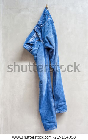 Unwashed blue jeans is hanging on the exposed concrete wall in bathroom. - stock photo