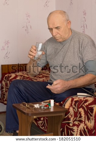 Unwell handicapped senior man sitting on a sofa at home taking medication swallowing down his pills with a glass of water - stock photo