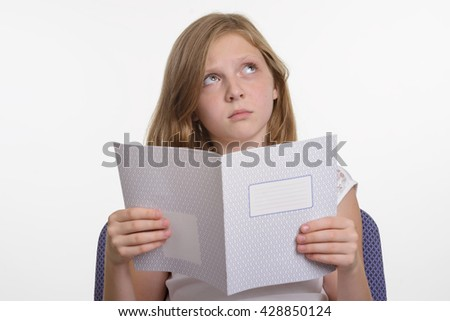 Unwillingness for studying. Little girl is upset and looks upwards with sad eyes. Child holds a copybook in her hands. Young kid is not interested in education. - stock photo