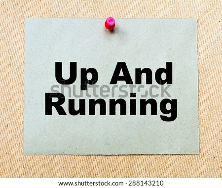 Up And Running  written on paper note pinned with red thumbtack on wooden board. Business conceptual Image - stock photo
